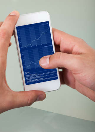 Closeup of hands checking stock market on smart phone in office photo