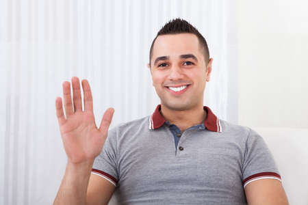 chat room: Portrait of happy young man waving at home Stock Photo
