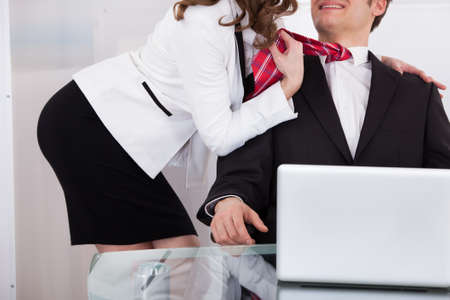 nude woman sitting: Young businesswoman pulling male colleagues tie while seducing him at desk in office Stock Photo