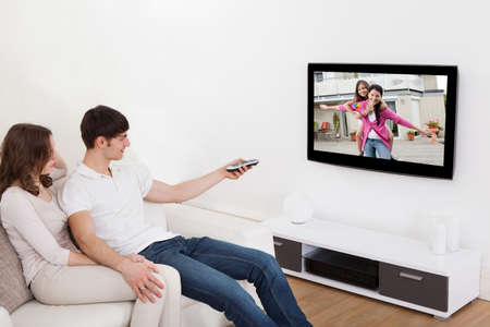 Young Couple In Livingroom Sitting On Couch Watching Television Stock Photo
