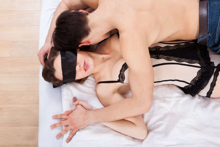 intimate sex: Side view of young man kissing sexy blindfolded woman in bed at home