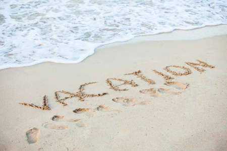writing western: Word Vacation written in sand on beach Stock Photo