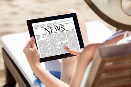Woman reading newspaper on digital tablet while relaxing on deck chair at beach photo