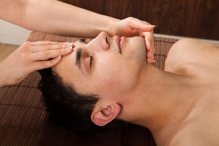 Side view of young man receiving head massage from massager in spa photo