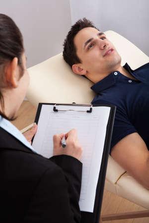 terapia psicologica: Masculino comunicación paciente mientras psicólogo escribir notas en el portapapeles en la clínica