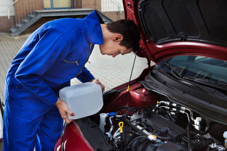 antifreeze: Side view of young mechanic pouring antifreeze into windscreen water tank on street Stock Photo