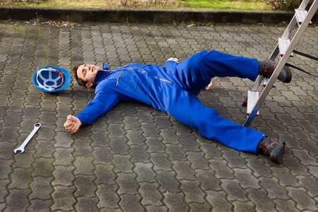 Volledige lengte van jonge onbewuste technicus viel van de ladder op straat