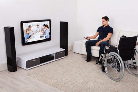 Full length of young handicapped man watching television in living room photo