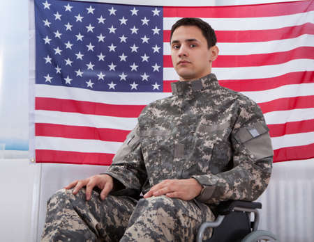 american soldier: Cropped image of patriotic soldier sitting on wheel chair against American flag