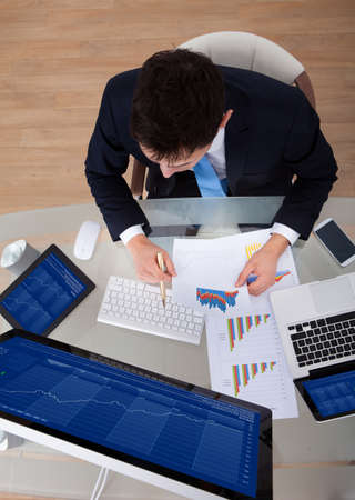 High angle view of businessman examining graphs at desk in office photo