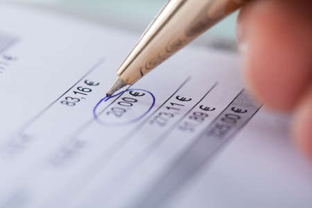 examiner: Hand circling 20 euros with pen on tax statement Stock Photo