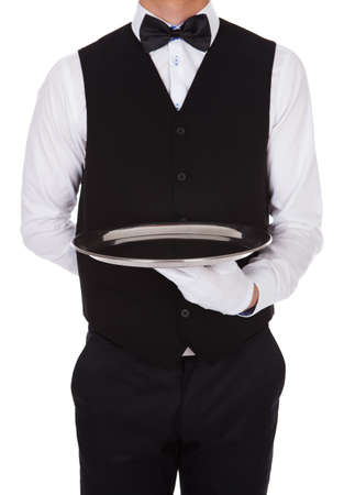 Midsection of waiter holding empty tray over white background Stock Photo