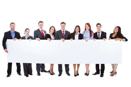 Large group of businesspeople presenting empty banner. Isolated on white photo