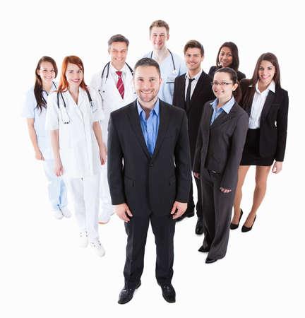 Patron debout sur le devant de son équipe de médecins et de gestionnaires