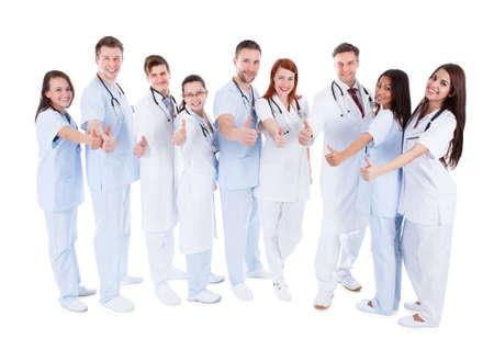 Diverse groep van jonge vrolijke artsen staan en zien thumbs up symbool van succesvolle professionele gezondheidszorg op een witte achtergrond Stockfoto
