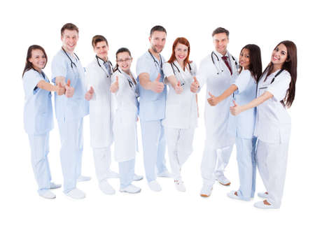 Diverse group of young cheerful doctors standing and showing thumbs up  symbol of successful professional healthcare  on white background Stock Photo