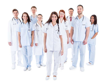 Large diverse group of medical staff in white uniforms standing grouped behind a handsome middle-aged bearded doctor or physician isolated on white