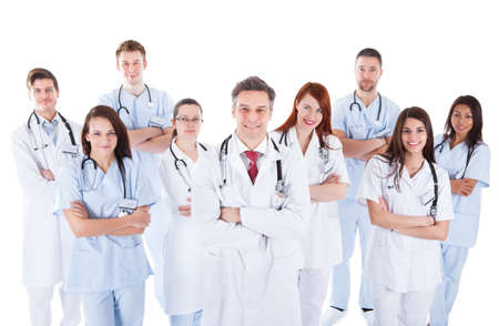 consultant physicians: Large diverse group of medical staff in white uniforms standing grouped behind a handsome middle-aged bearded doctor or physician isolated on white