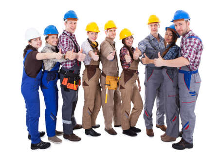 Diverse group of workmen and woman in their overalls and hardhats standing grouped in a semi circle giving a thumbs up gesture of approval and success  isolated on white photo