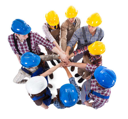 Large group of construction worker stacking hands. Isolated on white photo