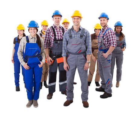 fontanero: Equipo diverso Confiado de obreros y mujeres de pie agrupados en sus petos y cascos sonriendo a la vista de alto �ngulo de la c�mara aislada en blanco Foto de archivo