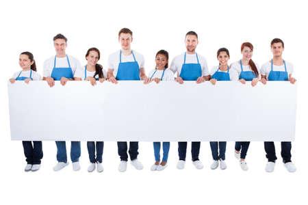 personal de limpieza: Numeroso grupo diverso de limpiadores o conserjes se usan delantales, con un cartel blanco en blanco con copia espacio para el texto aislado en blanco Foto de archivo