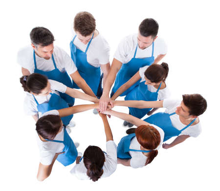 Cleaning team: High angle view of cleaners stacking hands over white background Stock Photo