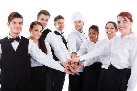 Obers en serveersters stapelen handen. Geïsoleerd op wit Stockfoto