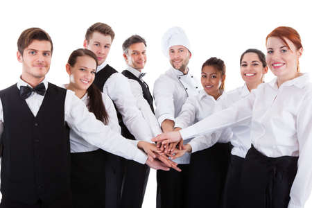 join the team: Waiters and waitresses stacking hands. Isolated on white