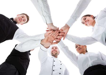 Kellner und Kellnerinnen Stapeln Hände. Isoliert auf weiß