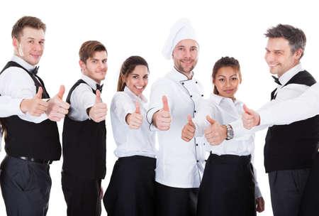 Obers en serveersters zien thumbs up teken. Geà ¯ soleerd op witte achtergrond