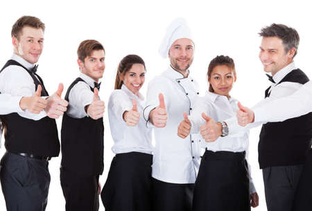 Waiters and waitresses showing thumbs up sign. Isolated on white background Standard-Bild