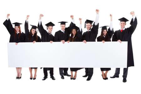 빈 배너를 보여주는 명랑 흥분 대학원생. 흰색에 고립