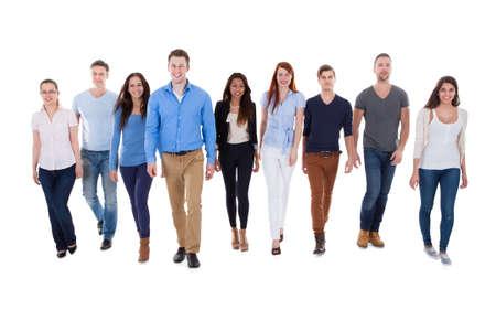 persona cammina: Gruppo eterogeneo di persone che camminano verso la telecamera. Isolati su bianco