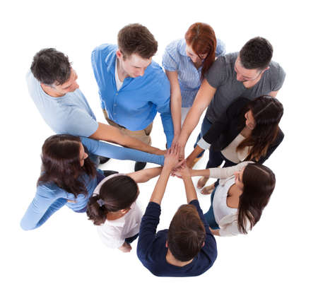 High angle view of people stacking hands together. Isolated on white