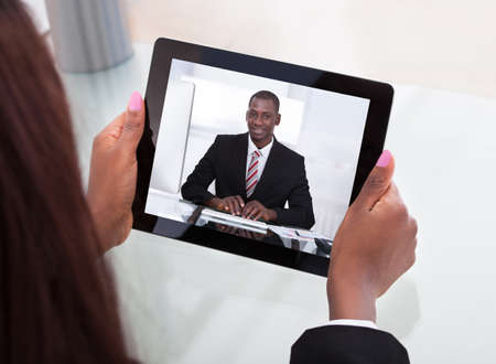 Cropped image of businesswoman attending video conference with colleague on digital tablet at desk in office Stock Photo