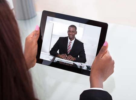 entrevista: Imagen recortada de negocios que asisten a una video conferencia con su colega sobre la tableta digital en el escritorio en la oficina