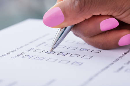 Cropped image of businesswomans hand filling customer survey form photo