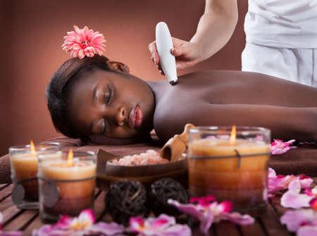 Zijaanzicht van jonge Afro-Amerikaanse vrouw die een microdermabrasie behandeling bij beauty spa
