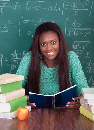 Portrait of confident female teacher writing in book at classroom desk photo