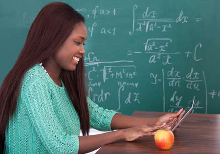 Portrait of confident female teacher holding digital tablet at school desk photo
