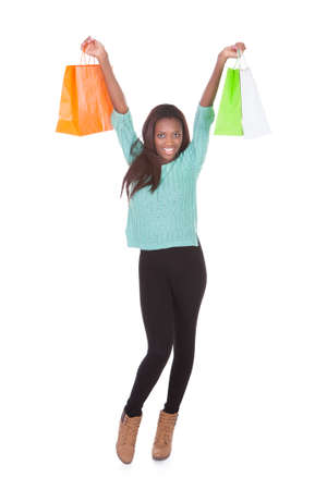 Full length portrait of African American woman carrying shopping bags against white background photo