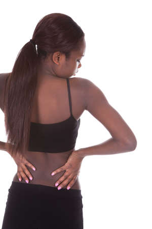 Rear view of young African American woman in undergarments suffering from backache over white background photo