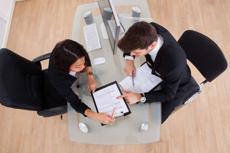 law suit: Business colleagues discussing over document in meeting Stock Photo