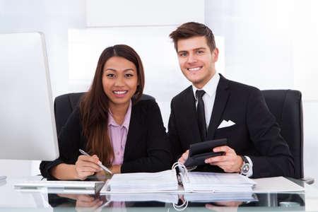 Compañeros de trabajo de cálculo de impuestos juntos en el escritorio en la oficina