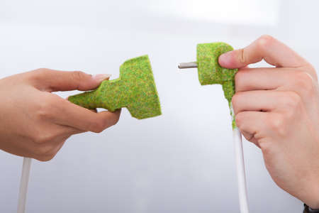Cropped image of hands fixing green plugs photo