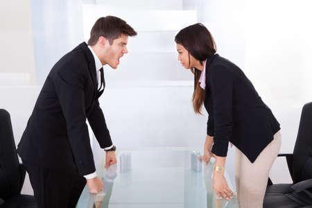 dominacion: Vista lateral de la gente de negocios que pelean en el escritorio en la oficina Foto de archivo