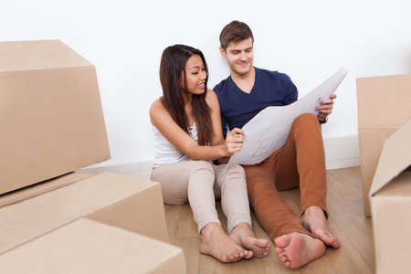 Young multiethnic couple looking at blueprint while sitting on floor in new home photo