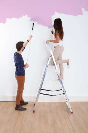 Full length of young couple painting new house photo