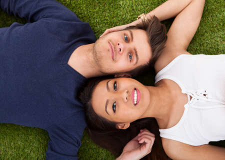 Directly above shot of young couple lying on grass in park photo